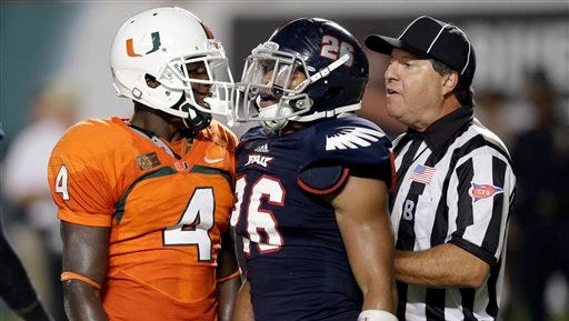 Back judge Barry Hendon, right, breaks up a tussle between Miami wide receiver Phillip Dorsett (4) and Florida Atlantic safety Jeremy McKnight (26) in 2013. Hendon is one of four local officials working Atlantic Coast Conference football games.