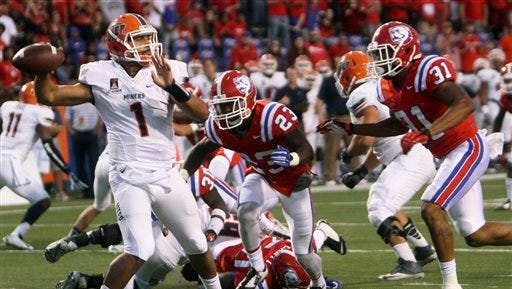 2014: UTEP's quarterback Jameill Showers (1) focuses on a player downfield despite pressure from Louisiana Tech defenders during the second quarter of an NCAA college football game Saturday, Oct. 4, 2014, in Ruston, La.