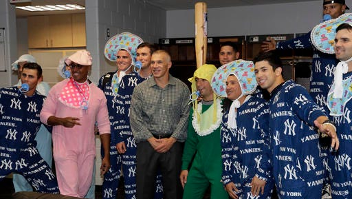 New York Yankees manager Joe Girardi, center, poses for a photo with Yankees' rookies wearing baby clothes after a during a baseball game against the Tampa Bay Rays Thursday, Sept. 22, 2016, in St. Petersburg, Fla.