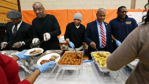 """Actor Delroy Lindo, second left, joined Newark Mayor Ras Baraka, second right, as they helped serve food at a Newark's Weequahic High School high school during an event to feed residents as part of a program to bring holiday cheer Friday, Dec. 23, 2016, in Newark, N.J. The London-born Lindo's lengthy film career includes roles in movies such as """"Crooklyn,"""" """"Malcolm X"""" and the TV series """"Blood and Oil"""" and """"The Chicago Code."""""""