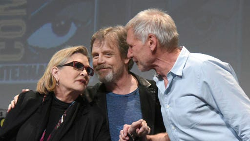 FILE - In this Friday, July 10, 2015 file photo, from left, Carrie Fisher, Mark Hamill and Harrison Ford attend a panel at Comic-Con International in San Diego, Calif. On Tuesday, Dec. 27, 2016, a family publicist said Fisher died at the age of 60. With the loss of several icons of Generation X's youth, the year 2016 has left the generation born between the early 1960s and the early 1980s, wallowing in memories and contemplating its own mortality.