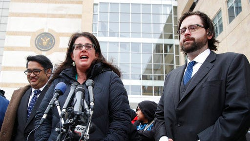 Becca Heller of the International Refugee Assistance Project, center, flanked by Omar Jadwat of the ACLU, left, and Justin Cox of the National Immigration Law Center, representing the plaintiffs, speaks to reporters outside court in Greenbelt, Md., Wednesday, March 15, 2017. A federal judge in Maryland says he will issue a ruling in a lawsuit challenging President Donald Trump's revised travel ban.