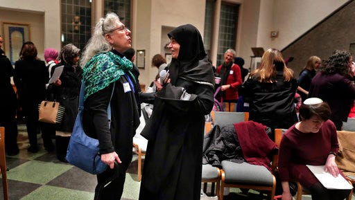 In this Thursday, Feb. 16, 2017 photo, members of the Sisterhood Salaam Shalom talk after a unity vigil held at the Jewish Theological Seminary in New York. The Sisterhood of Salaam Shalom, a national organization that brings together Muslim and Jewish women, organized the gathering as part of the organization's response to President Donald Trump's travel ban.