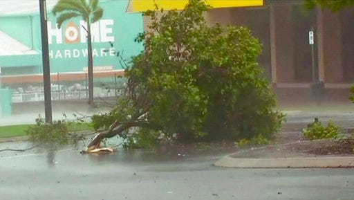 In this image made from video, tree debris lies on the street as wind gusts in Bowen, eastern Australia, Tuesday, March 28, 2017.  A powerful cyclone lashed islands, damaged roofs and cut power on Tuesday as it edged toward Australia's tropical northeast coast, officials said.