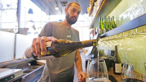 """This Wednesday, March 29, 2017, photo, Current Fish & Oyster Restaurant bartender Wren Kennedy pours wine behind the bar, in Salt Lake City. At Current Fish & Oyster Restaurant, a frosted glass wall covering a long, glossy bar will come down at the stroke of midnight on July 1, according to Joel LaSalle, one of the restaurant's owners. """"Not only is it ugly and covers up a beautiful bar, but it's costing us thousands of dollars in sales each month,"""" Some Utah restaurants are counting down the days until a new liquor law takes effect this summer, allowing eateries to take stop using walls and partitions that prevent customers from seeing their alcoholic drink being mixed and poured."""
