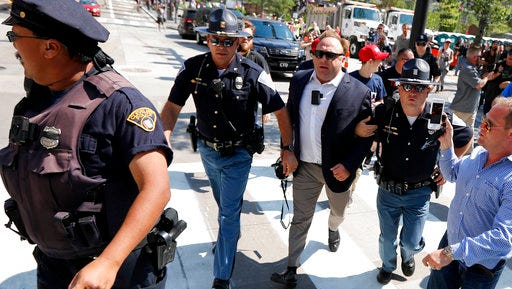 "FILE - In this file photo made Tuesday, July 19, 2016, Alex Jones, center right, is escorted by police out of a crowd of protesters outside the Republican convention in Cleveland. A lawyer defending Jones, a the right-wing radio host and conspiracy theorist, in a child-custody dispute said Jones is a ""performance artist"" whose on-air persona differs from the private man. The Austin American-Statesman reported that Kelly Jones described her ex-husband at a recent pretrial hearing in Austin as ""not a stable person."""