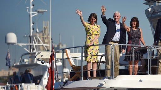 U.S. Vice President Mike Pence, center, his wife Karen, right, and New South Wales Premier Gladys Berejiklian wave during a cruise on the harbor in Sydney, Sunday, April 23, 2017. Pence is on the last part of his four-country trip to Asia and Australia.