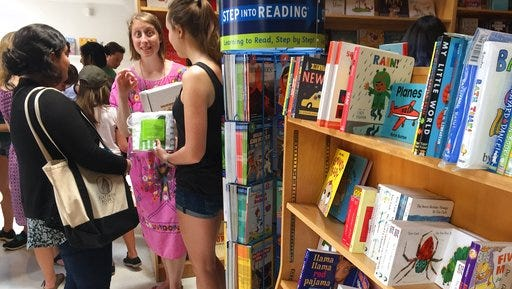 In this April 29, 2017 photo, Author Emma Straub, center, chats with customers on the opening day for the new Books are Magic bookstore in Brooklyn, New York, which she owns with her husband. They decided to open the store after another beloved neighborhood bookstore closed. Straub is one of a number of authors who own bookstores around the country, including Ann Patchett and Jeff Kinney.