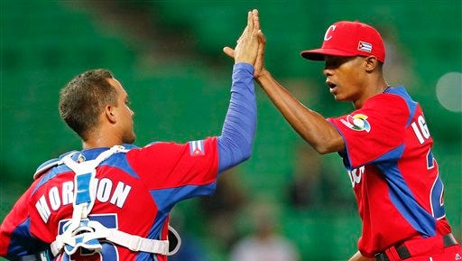 Cuban catcher Frank Morejon (left) and pitcher Raisel Iglesias celebrate after defeating Brazil during the 2013 World Baseball Classic.