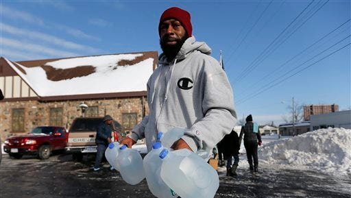 Lemott Thomas carries water that was being distributed for free at the Lincoln Park United Methodist Church in Flint on Tuesday, Feb. 3, 2015. The city gets tap water from the Flint River, but residents have complained about the smell, taste and appearance. The city says the water is safe to drink.