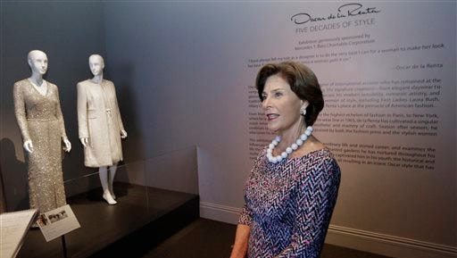 This photo shows former first lady Laura Bush speaks during an interview next to her Oscar de la Renta dress and coat she wore to the swearing-in ceremony at her husband?s 2005 inauguration that are on display in Dallas. The ensembles are among more than 60 featured in a new retrospective on de la Renta?s career that opens Saturday at the George W. Bush Library and Museum. ?Oscar de la Renta: Five Decades of Style,? which runs through Oct. 5, features designs worn by everyone from celebrities to socialites to first ladies.