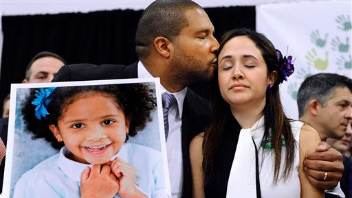 Jimmy Greene, left, kisses his wife Nelba Marquez-Greene as he holds a portrait of their daughter, Sandy Hook School shooting victim Ana Marquez-Greene, at a news conference in Newtown, Conn. Jimmy Greene, an internationally acclaimed jazz saxophonist, composer and bandleader, is preparing an album, called ?A Beautiful Life,? inspired by his daughter. He plans to play selections from the album Sunday at the Litchfield, Conn., Jazz Festival.