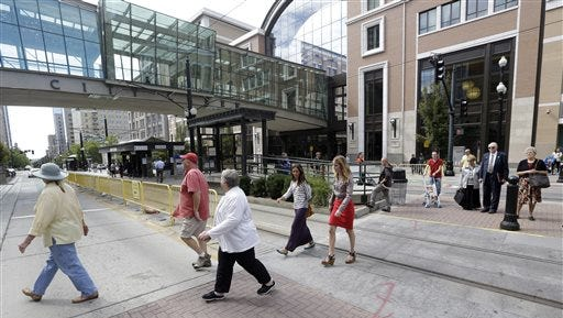 In this Sept. 24, 2013 file photo, people walking across the street in front of the City Creek shopping center in Salt Lake City. Jack Harry Stiles who faced up to 15 years in prison in an alleged mass shooting plot at an upscale mall has been sentenced to probation and is receiving mental health treatment. A civil lawsuit filed by the mall has also been dismissed after Stiles agreed stay away from City Creek Center, documents show. Stiles defense attorney said today he is responding well to treatment.