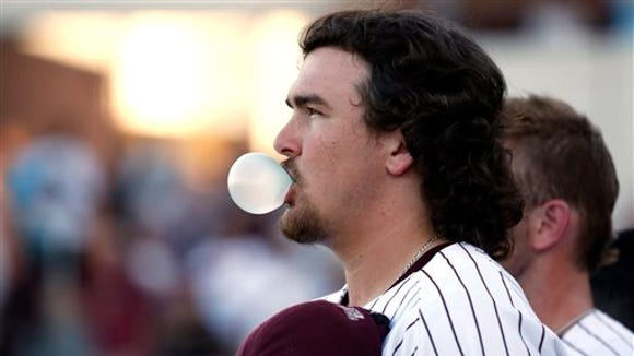 Mississippi State baseball pitcher Jonathan Holder blows a bubble during the playing of the National Anthem prior to their game against Central Arkansas in their NCAA college baseball regional championship  tournament game in Starkville, Miss., Monday June 3, 2013. (AP Photo/Rogelio V. Solis)
