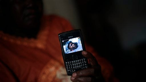Musu Kobba of Monrovia, Liberia, holds a smartphone with the picture of her sister Saah David, an Ebola victim. Six months into the outbreak in West Africa, the amount of aid reaching those who are suffering is still insufficient.