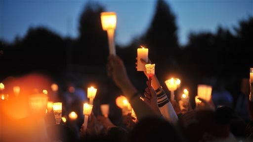 In this June 10, 2014 photo, people participate in a candlelight vigil for Emilio Hoffman, the victim of a shooting at Reynolds High School on Tuesday, in Troutdale, Ore. Authorities said a teen gunman armed with a rifle shot and killed the 14-year-old student and injured a teacher before he likely killed himself at the high school.