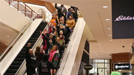 Protesters of the grand jury decision in the Michael Brown shooting chant slogans at the St. Louis Galleria mall on Wednesday evening in Richmond Heights, Mo. They stayed in the mall for about 15 minutes and then left peacefully without confrontation with a large police presence.