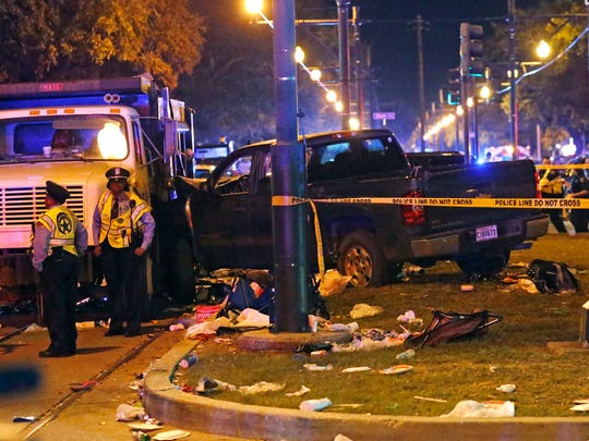Police stand next to a pickup truck that slammed into a crowd and other vehicles, causing multiple injuries, coming to a stop against a dump truck, during the Krewe of Endymion parade in New Orleans, Saturday, Feb. 25, 2017.