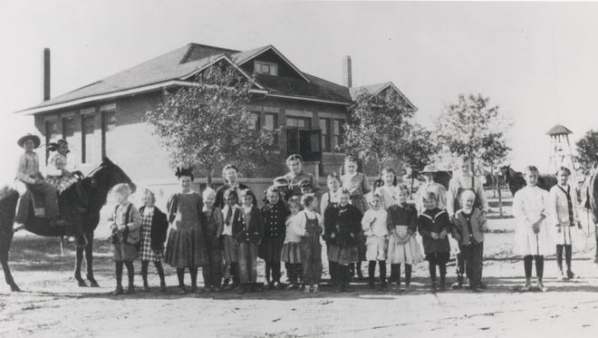 Students and teachers gather in front of the Scottsdale Grammar School, now known as the Little Red Schoolhouse, which dates back to before statehood.