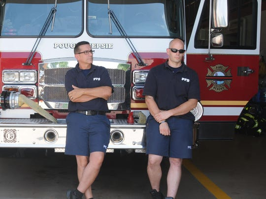Firefighters Ed Cefarelli, left, and Ken Deichler, right, sit in the garage of the Public Safety Building on Main Street in the City of Poughkeepsie.