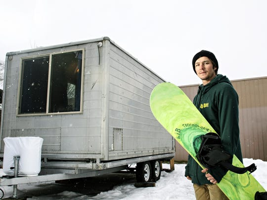 Pro snowboarder Jason Robinson stands in front of his small house built on a trailer.