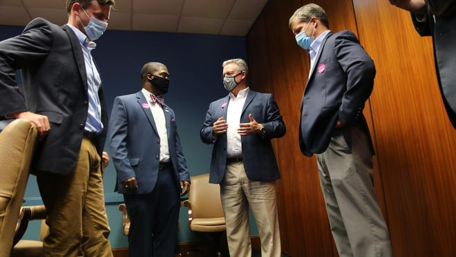 Sen. Jim Perry, center, talks with Chief of Staff Andrew Tripp with Sen. Phil Berger's office, left, Kinston Mayor Dontario Hardy, and General Counsel Brian Fork with Berger's office after a flood mitigation meeting inside Lenoir Community College's boardroom Tuesday, Aug. 25.