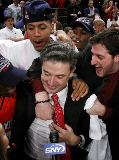 U of L head coach Rick Pitino, center, is embraced by players Russ Smith, #2, left, and Mike Marra, #33, after they defeated Cincinnat to win the Big East championship at Madison Square Garden in New York City. Mar. 10, 2012