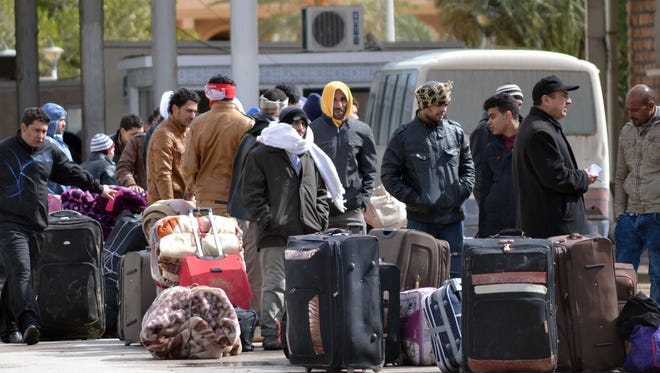Egyptians wait in Ras Jdir in Tunisia on Feb. 23 as they head to Djerba airport, on the Tunisian-Libyan border, for a flight evacuating them to Cairo.