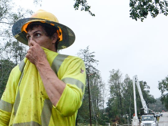 A worker for Pike electric looks at damage along Robinson Bridge Road in Liberty early Monday.