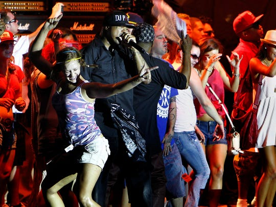 Three 6 Mafia's DJ Paul (middle) dances with dozens of fans at the Orion Stage during the first day of Memphis in May's Beale St. Music Festival. (Mark Weber/The Commercial Appeal)