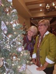 "Susan Reagan, left, and Tuck Harvey consider bidding on a decorated tree at the 2017 ""Oh Christmas Tree"" event, a fundraiser for Interfaith Ministries. The silent auction, to be held at The Forum, will include themed trees decorated by area artists."