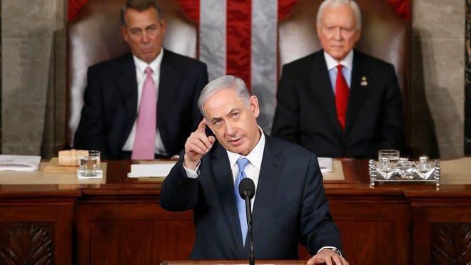 Israeli Prime Minister Benjamin Netanyahu gestures as he speaks before a joint meeting of Congress on Capitol Hill in Washington, Tuesday, March 3, 2015. House Speaker John Boehner of Ohio, left, and Sen. Orrin Hatch, R-Utah, listen.