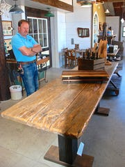 Paul Jensen looks at a table he fashioned from planks