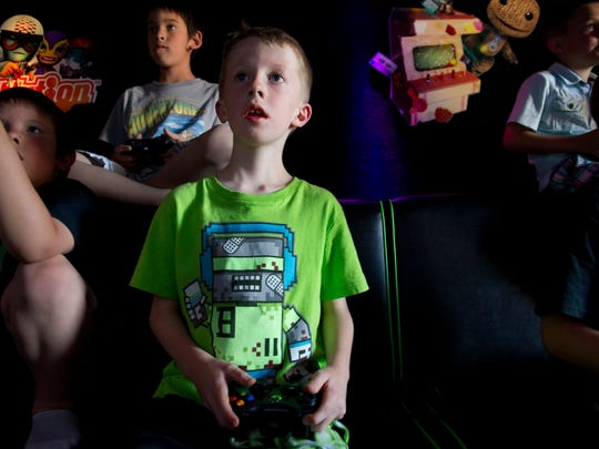 Noah Doris, 6, plays the Xbox game Minecraft during the grand opening for Curbside Gaming in Spanish Springs on June 28.