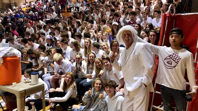 This image was captured on March 11, 2020, the last night high school sports were played in New Hampshire. To the right, dressed in all white, is Portsmouth High School Athletic Director Rus Wilson with students during the Clippers' Division I boys basketball playoff game against Manchester Central.