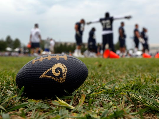 A toy football rests in the grass as members of the St. Louis Rams work out during training camp at the NFL football team's practice facility on Saturday, July 26, 2014, in St. Louis. (AP Photo/Jeff Roberson)