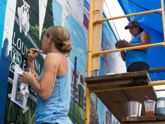 Brooke Foy and Emery Thibodeaux, right, paint a postcard-style