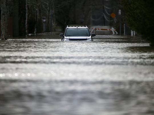 A vehicle is submerged along Waits Avenue in California, Sunday, Feb. 25, 2018, in Cincinnati. The Ohio River is expected to crest at 60.7 feet by Sunday evening, according to the National Weather Service. The river rose above the 60 feet mark for the first time in two decades Sunday morning.