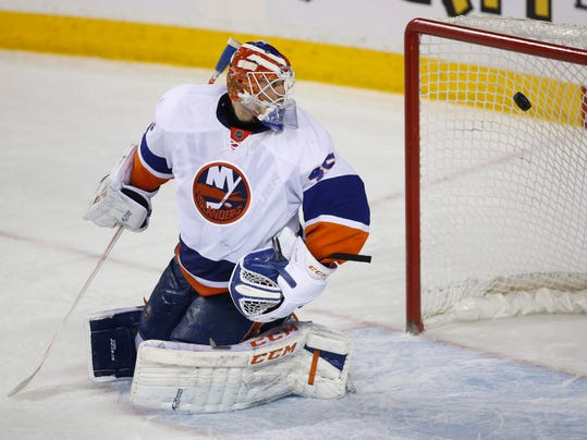 New York Islanders goalie Anders Nilsson, of Sweden, looks back at his net as Calgary Flames' Joe Colborne, not shown, scores the game winning goal during third period NHL hockey action in Calgary, Alberta, Friday, March 7, 2014. (AP Photo/The Canadian Press, Jeff McIntosh)