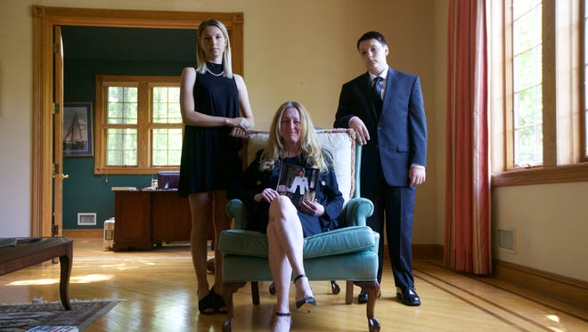 James Clarke's children, Laura and Peter, stand with his wife, Jane.
