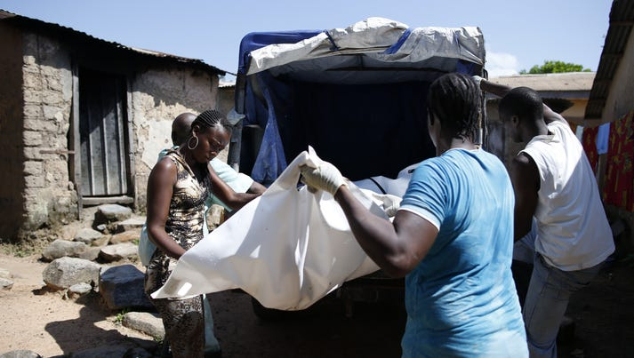 Health workers carry the body of a victim of the Ebola