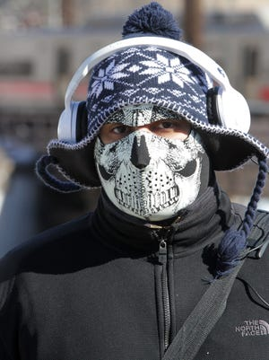 Gregory Paulino of Port Chester wears a face mask while walking in sub-freezing weather on Friday. He was on his way to a gym to work out.