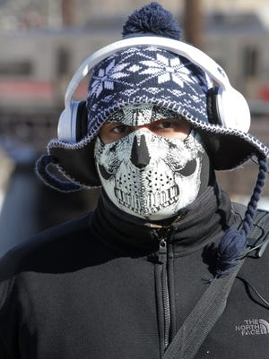 Gregory Paulino of Port Chester wears a skull-patterned face mask while walking in sub-freezing weather Feb. 13.