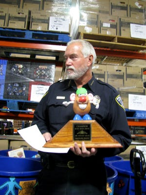 Aztec police Chief Mike Heal holds the traveling trophy Thursday at the ECHO Food Bank in Farmington after his city won an annual food collection competition among other local governments.