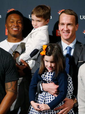 Denver Broncos quarterback Peyton Manning holds his 5-year-old daughter Mosley, while Broncos wide receiver Demaryius Thomas holds Manning's son, Marshall, after Manning announced his retirement at team headquarters Monday, March 7, 2016, in Englewood, Colo. Manning, who has been in the NFL for the past 18 years, is retiring after winning five MVP trophies and two Super Bowl championships, the most recent last month against the Carolina Panthers.