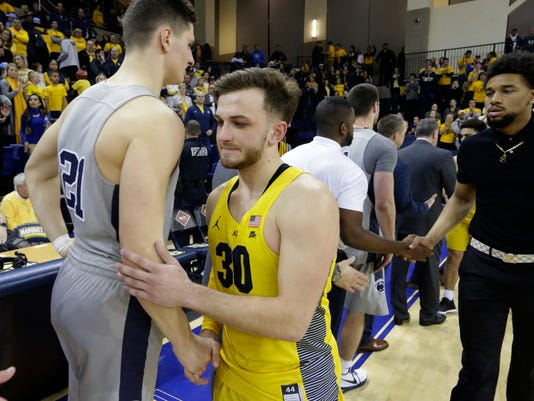 Marquette guard Andrew Rowsey (30) shakes hands with Penn State's John Harrar after Penn State's 85-80 win in an NCAA college basketball game in the NIT on Tuesday, March 20, 2018, in Milwaukee. (Mark Hoffman/Milwaukee Journal-Sentinel via AP)