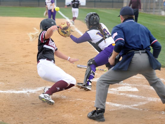 McMurry's Adrienne Nairn (12) slides into home ahead