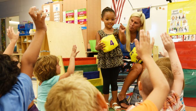 Samantha Norris chooses a student to answer a question during Zane Grey Elementary School kindergarten jumpstart program. At right is teacher Wendy Winland.