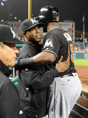 Miami Marlins center fielder Marcell Ozuna (13) is hugged by hitting coach Barry Bonds (25) after scoring a run against the Washington Nationals during the second inning at Nationals Park.