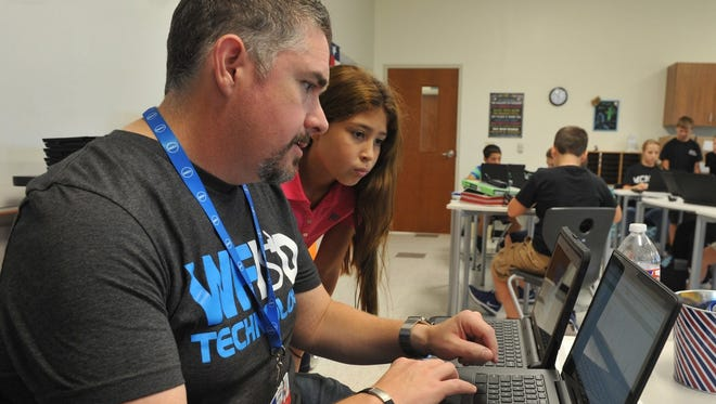 In this file photo, Shad McGaha, chief technology officer for the Wichita Falls ISD, helps Isabella Duron, a McNiel Middle School student, with the login on her new Chromebook. The WFISD recently installed its own dark-fiber network, allowing the largest school district in North Texas control its network and infrastructure.